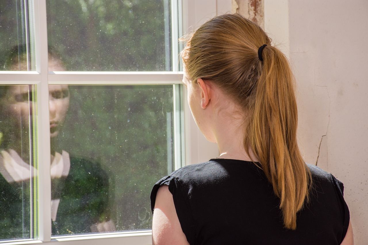 woman watching her reflection in a window pane in lucid dreaming